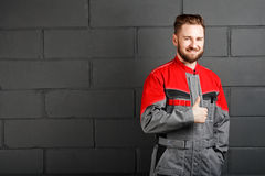 Portriat of smiling man wearing overalls near brick wall Stock Images