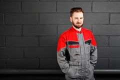 Portriat of smiling man wearing overalls near brick wall Royalty Free Stock Image
