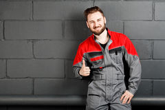 Portriat of smiling man wearing overalls near brick wall Stock Photo