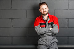 Portriat of smiling man wearing overalls near brick wall Royalty Free Stock Photo