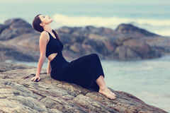 Portriat of Young redhead woman in a black dress. Near the ocean Royalty Free Stock Image