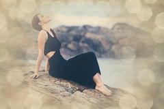 Portriat of Young redhead woman in a black dress. Near the ocean Royalty Free Stock Photography