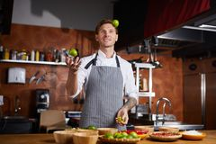 Chef Juggling Citrus. Portrit of handsome chef juggling limes standing at table with spices, copy space royalty free stock image