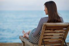 Portrit im Freien der schönen jungen Frau, die an der Seeküste am Abend sich entspannt stockfoto
