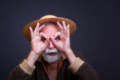 Portrrait des lustigen älteren Mannes mit Strohhut Stockbild