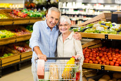 Portrsit of happy senior couple with cart. At the grocery shop Royalty Free Stock Photos