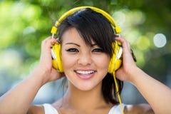 Porträt der athletischen Frau gelbe Kopfhörer tragend und Musik genießend Lizenzfreie Stockfotos