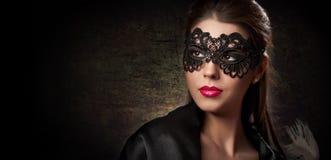 Porträt der attraktiven sinnlichen jungen Frau mit Maske. Junge attraktive Brunettedame, die auf dunklem Hintergrund im Studio auf Stockbilder