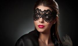 Porträt der attraktiven sinnlichen jungen Frau mit Maske. Junge attraktive Brunettedame, die auf dunklem Hintergrund im Studio auf Stockfotos