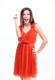 Porträt der aufgeregten überraschten jungen Frau im roten Kleid Stockfotografie