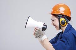 Porträt der ausdrucksvollen kaukasischen Frau mit dem Lautsprecher-Horn, das im Hardhat aufwirft Lizenzfreie Stockfotografie