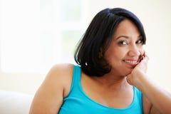 Porträt der überladenen Frau sitzend auf Sofa Stockbild