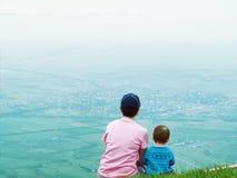 Porträt der Familienmutter und des Babysohns, die zusammen in der Natur sitzen Lizenzfreie Stockfotografie