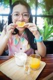 Porträt der glücklichen asiatischen Frau in einem Café mit orange Früchten gegen einen Mund wie ein Lächeln, sagen das Käsekonzep Lizenzfreie Stockfotos