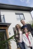 Porträt der glücklichen Familie außerhalb des neuen Hauses Lizenzfreie Stockfotos