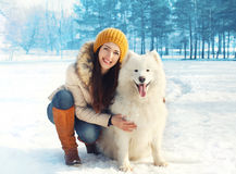 Porträt der glücklichen Frau mit weißem Samoyed verfolgen draußen Stockbild