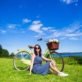 Porträt der glücklichen Frau sitzend auf dem Gras mit Weinlese bicycl Stockfotografie