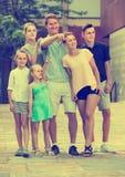 Porträt der glücklichen großen Familie, die mit Fingerberufskleidung zeigend steht Lizenzfreies Stockfoto