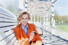 Porträt der glücklichen lächelnden Geschäftsfrau oder des Modestudenten mit der Sonnenbrille, die auf der Bank im Park, Leutekonz Lizenzfreie Stockfotos