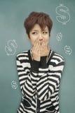 Porträt der jungen Frau ihren Mund vor Tafel mit Dollarzeichen bedeckend Lizenzfreies Stockfoto