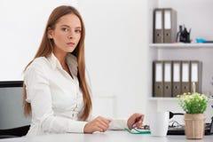 Porträt der jungen Geschäftsfrau, die in ihrem Büro arbeitet Stockfotografie