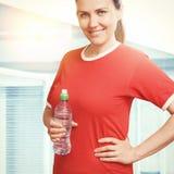Porträt der jungen lächelnden Frau, die Wasserflasche hält Stockfotografie