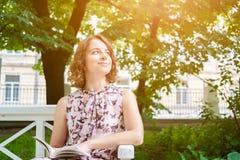 Porträt der kaukasischen Frau im Sommerkleid auf Parkbank Lizenzfreie Stockfotos