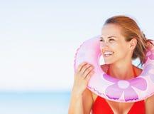 Porträt der lächelnden jungen Frau auf Strand mit dem Schwimmenringschauen Stockfotografie