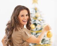 Porträt der lächelnden jungen Frau, die Weihnachtsbaum verziert Lizenzfreies Stockbild
