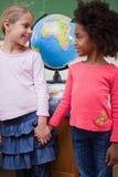 Porträt der lächelnden Schulmädchen, die Hände halten Lizenzfreie Stockbilder