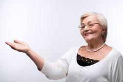 Porträt der reizenden Großmutter Kopienraum zeigend Lizenzfreies Stockfoto
