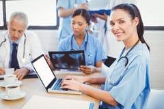 Porträt der Ärztin unter Verwendung des Laptops Stockbilder