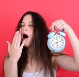 Porträt der schläfrigen jungen Frau im Chaos, das Uhr gegen r hält Stockbilder