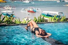 Porträt der schönen gebräunten Frau in der schwarzen Badebekleidung, die im Swimmingpoolbadekurort sich entspannt Heißer Sommerta Stockfoto