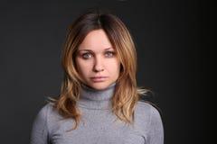 Porträt der schönen jungen Frau gegen schwarzen Hintergrund im Studio Stockfoto