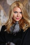 Porträt der schönen jungen Frau mit dem blonden Haar, das den modernen Pelzmantel betrachtet Kamera trägt Stockbild