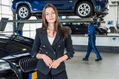 Porträt der schönen jungen Geschäftsfrau In Car Garage Stockbild