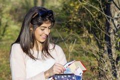 Porträt der schönen lachenden Frau, die ihr Geld im Park zählt Stockfotografie