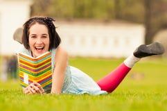 Porträt der schönen lächelnden Frau, die auf Graslesebuch liegt Lizenzfreie Stockfotos