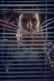 Porträt der schönen mysteriösen Frau, die durch Jalousie, Jalousie schaut Lizenzfreie Stockfotografie