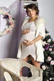 Porträt der schönen schwangeren jungen Frau nahe einem Weihnachtsbaum Stockbilder