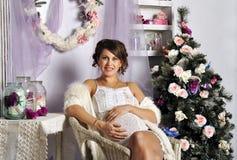 Porträt der schönen schwangeren jungen Frau nahe einem Weihnachtsbaum Stockfotos