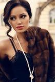 Porträt der schönen sexy Frau mit dem dunklen Haar im luxuriösen Pelzmantel Stockfotos