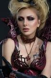 Porträt der schönen Teufelfrau im dunklen sexy Kleid Stockbild