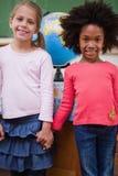 Porträt der Schulmädchen, die Hände halten Lizenzfreies Stockbild