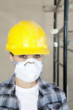 Porträt der tragenden Atemschutzmaske der Arbeitnehmerin an der Baustelle Lizenzfreie Stockfotografie