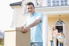Porträt der tragenden Pappschachtel des überzeugten Mannes bei der Bewegung des Hauses mit Familie im Hintergrund Lizenzfreies Stockfoto