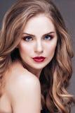 Porträt der wunderbaren jungen blonden Frau mit dem langen Haar, das Kamera, lächelnd betrachtet Stockfoto