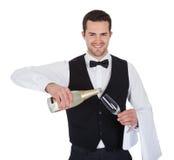 Porträt des auslaufenden Champagners des Butlers in Glas Lizenzfreie Stockbilder