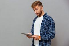 Porträt des überraschten zufälligen Mannes, der Tablet-Computer verwendet Lizenzfreie Stockbilder
